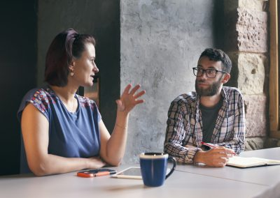Digital Transformation Agency Director talks to a team member at a table over a coffee