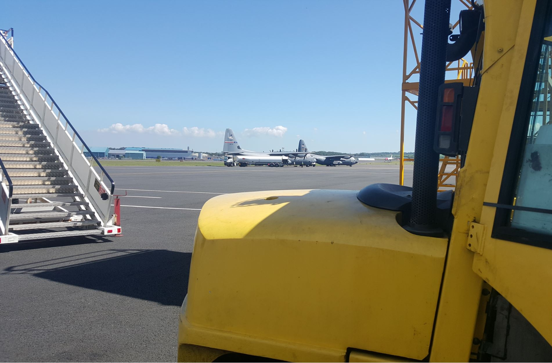 Yellow vehicle parked on the runway of an airport with plans on the tarmac in the background