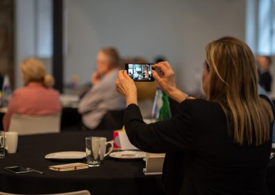 A woman is an a business event, holding her camera up to film the speaker