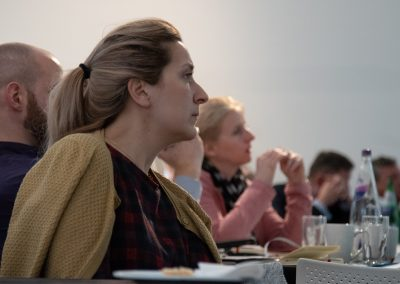 The audience at a business event, watching the speaker