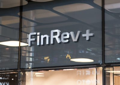 Signage above a glass office door, showing FinRev Plus logo