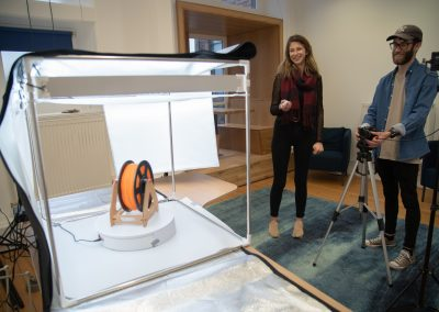 Photographer and assistant behind the camera, taking shots of product on a turntable for 360 degree images